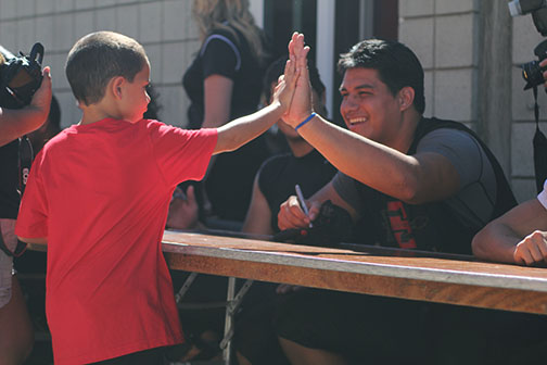 Young fan high-fives senior defensive lineman Sam Meredith