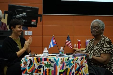 Georgina Herrera mira hacia el publico sorprendida por el recibimiento mientras que la profesora Norma Iglesias-Prieto le aplaude a la poeta. Foto de Jose Guzman